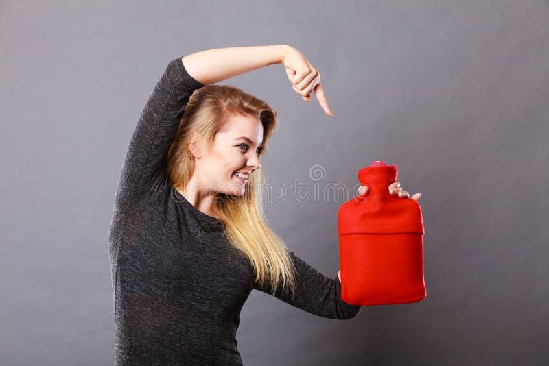 Γυναίκα που κρατά το θερμό κόκκινο - μπουκάλι ζεστού νερού στοκ εικόνες