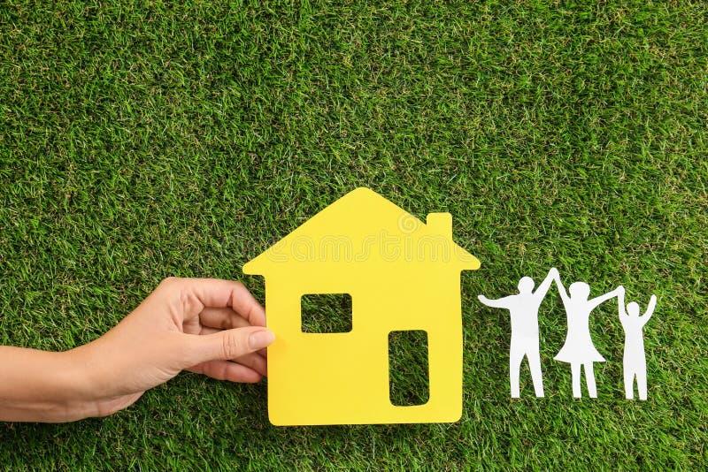 Γυναίκα που κρατά το κίτρινο σπίτι εγγράφου κοντά στους αριθμούς της ευτυχούς οικογένειας στην πράσινη χλόη, στοκ εικόνες
