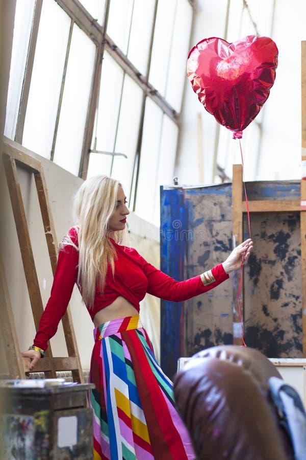 γυναίκα που κρατά το κόκκινο μπαλόνι στη μορφή μιας καρδιάς στοκ εικόνα