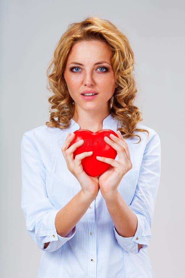 Γυναίκα που κρατά το κόκκινο σύμβολο καρδιών στοκ εικόνα με δικαίωμα ελεύθερης χρήσης