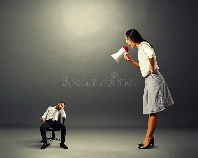 Γυναίκα που κραυγάζει στο μικρό οκνηρό άνδρα στοκ εικόνα