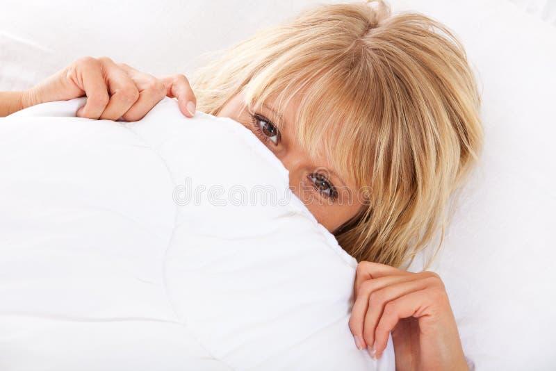 Γυναίκα που κρύβει το πρόσωπό της στο πλαίσιο του φύλλου στοκ εικόνες