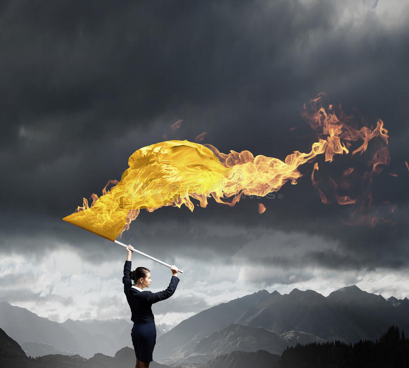 Γυναίκα που κυματίζει την κίτρινη σημαία στοκ φωτογραφία με δικαίωμα ελεύθερης χρήσης