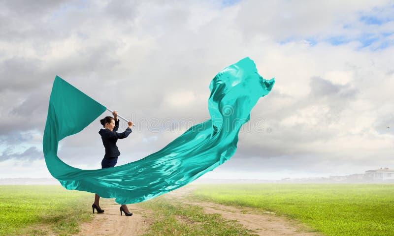 Γυναίκα που κυματίζει την μπλε σημαία στοκ φωτογραφίες