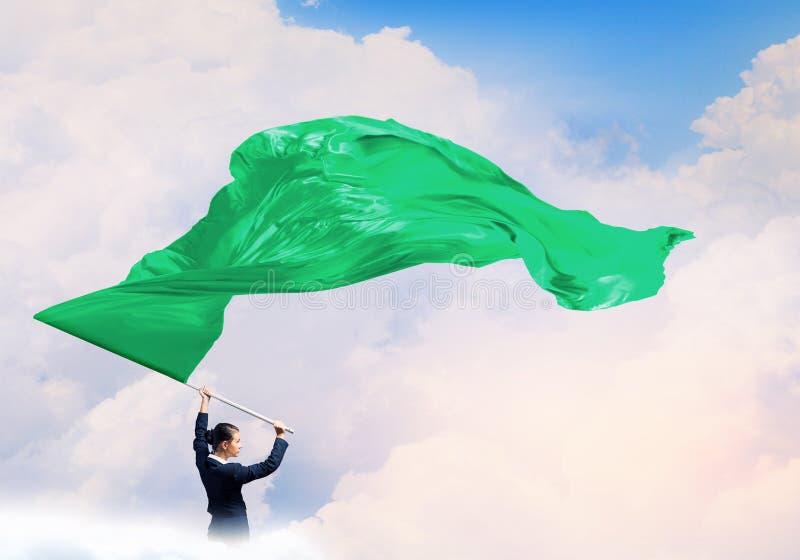 Γυναίκα που κυματίζει την πράσινη σημαία στοκ φωτογραφία με δικαίωμα ελεύθερης χρήσης