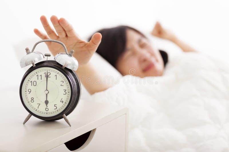 Γυναίκα που κλείνει το ξυπνητήρι στο κρεβάτι στοκ εικόνες