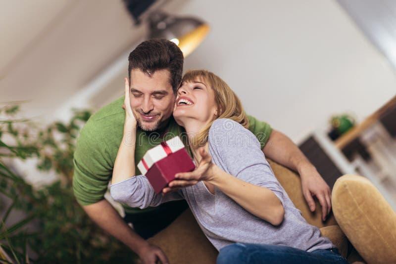 Γυναίκα που λαμβάνει ένα παρόν από το φίλο της καθμένος στον καναπέ στοκ φωτογραφία
