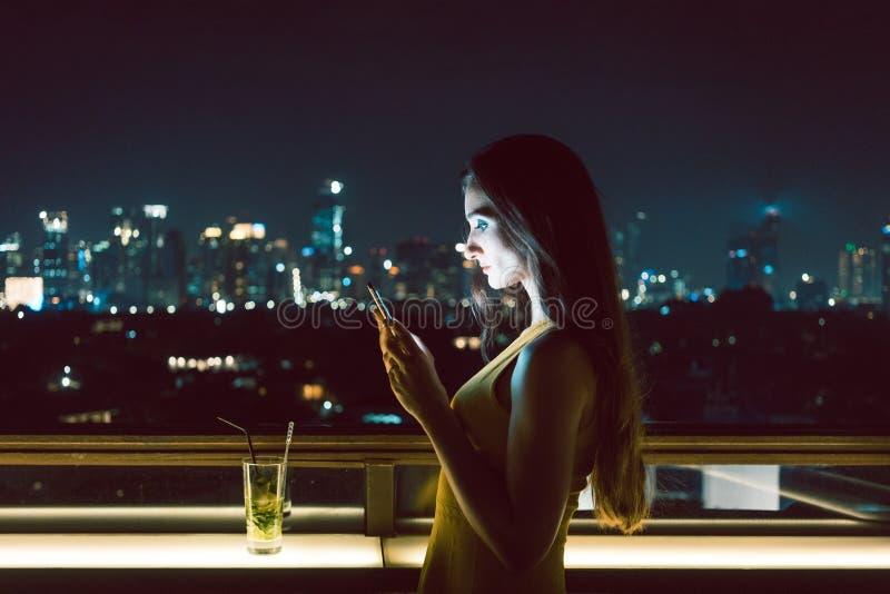 Γυναίκα που λαμβάνει το λυπημένο μήνυμα στο έξυπνο τηλέφωνο στοκ φωτογραφία