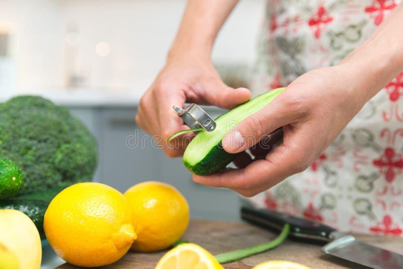 Γυναίκα που μαγειρεύει τα υγιή τρόφιμα στην κουζίνα της, ξεφλουδίζει ένα φρέσκο αγγούρι στον τεμαχίζοντας πίνακα στοκ εικόνες με δικαίωμα ελεύθερης χρήσης