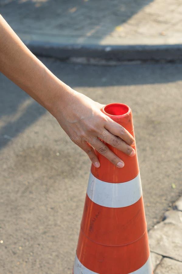Γυναίκα που μαζεύει με το χέρι τον κώνο κυκλοφορίας στοκ εικόνες