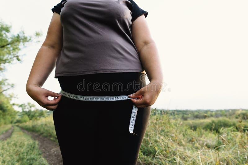 Γυναίκα που μετρά τα ισχία της με την ταινία μέτρου στοκ φωτογραφίες με δικαίωμα ελεύθερης χρήσης