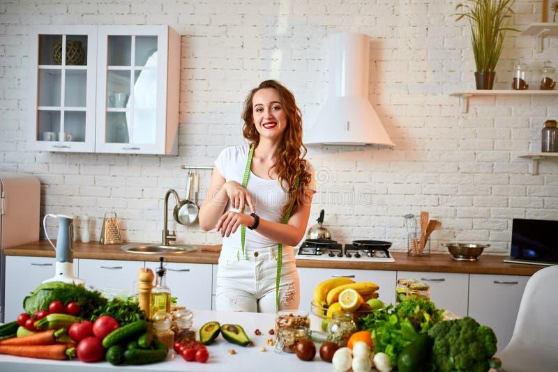 Γυναίκα που μετρά την τέλεια μορφή της όμορφης μέσης με το πράσινο εκατοστόμετρο ταινιών Υγιείς τρόπος ζωής και κατανάλωση Υγεία, στοκ εικόνες