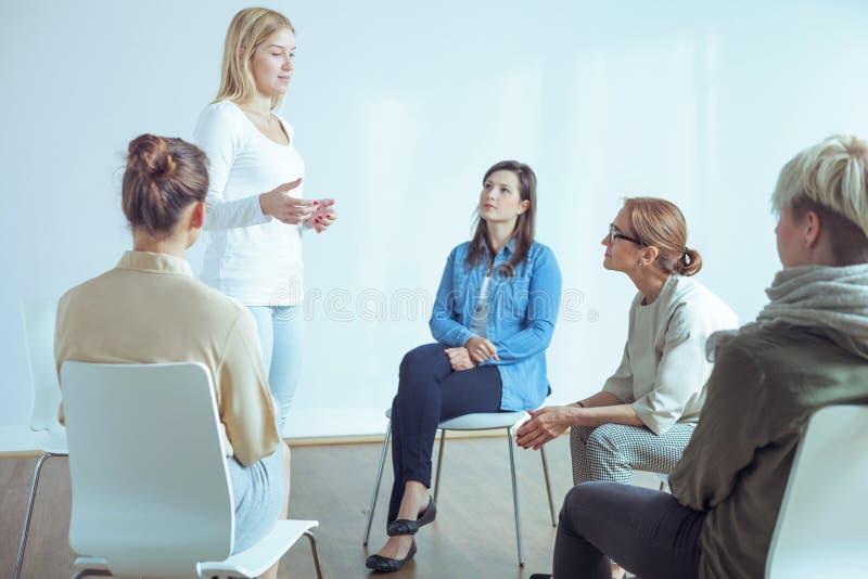Γυναίκα που μιλά για τα προβλήματα κατά τη διάρκεια της συνεδρίασης της ομάδας στήριξης με τον ψυχοθεραπευτή στοκ εικόνα με δικαίωμα ελεύθερης χρήσης