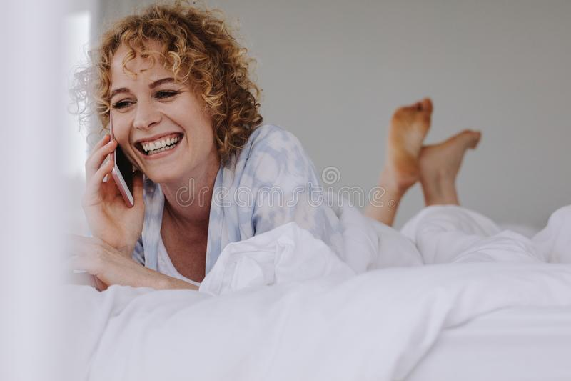 Γυναίκα που μιλά στο κινητό τηλέφωνο που βρίσκεται στο κρεβάτι στοκ φωτογραφία