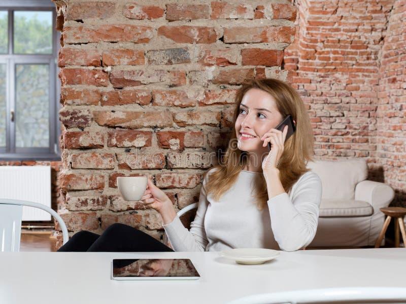 Γυναίκα που μιλά στο τηλέφωνο και τον καφέ κατανάλωσης στοκ εικόνα με δικαίωμα ελεύθερης χρήσης