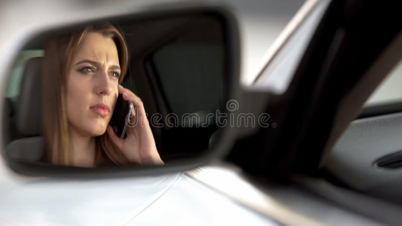 Γυναίκα που μιλά στο τηλέφωνο οδηγώντας, απρόσεκτος στο δρόμο, οπισθοσκόπος καθρέφτης στοκ εικόνες