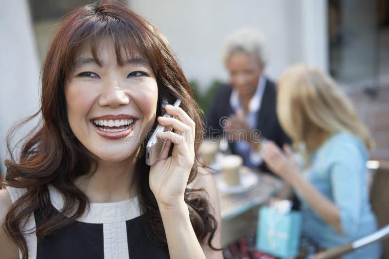 Γυναίκα που μιλά στο τηλέφωνο, φίλοι που πίνει τον καφέ στοκ εικόνα