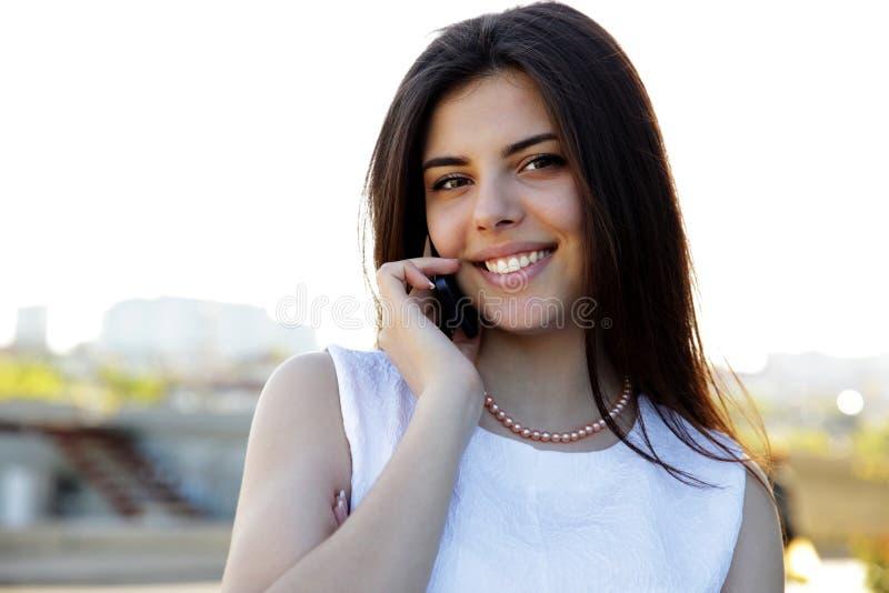 Γυναίκα που μιλά στο τηλέφωνο υπαίθρια στοκ εικόνα