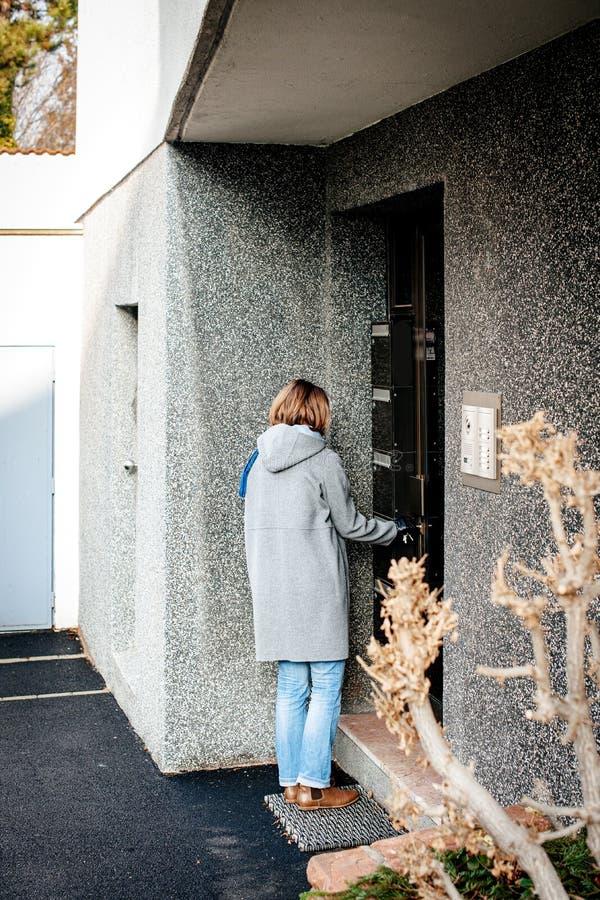 Γυναίκα που μπαίνει στη ανοιχτή πόρτα πολυκατοικίας με το βασικό κλείσιμο στοκ φωτογραφία με δικαίωμα ελεύθερης χρήσης