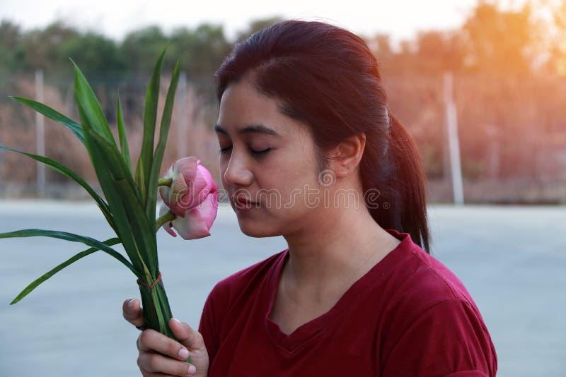 Γυναίκα που μυρίζει ειρηνικά το ρόδινο λωτό στην ανθοδέσμη στοκ φωτογραφίες με δικαίωμα ελεύθερης χρήσης