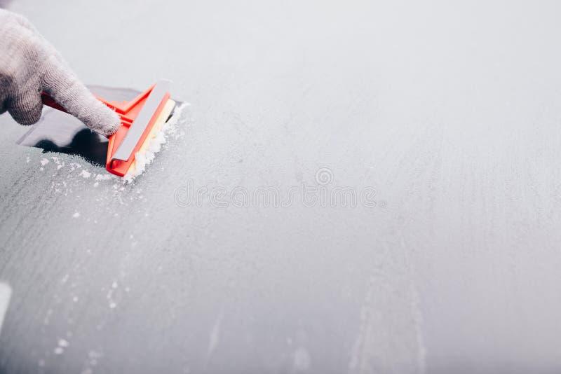Γυναίκα που ξύνει τον παγωμένο μπροστινό ανεμοφράκτη αυτοκινήτων στοκ εικόνα
