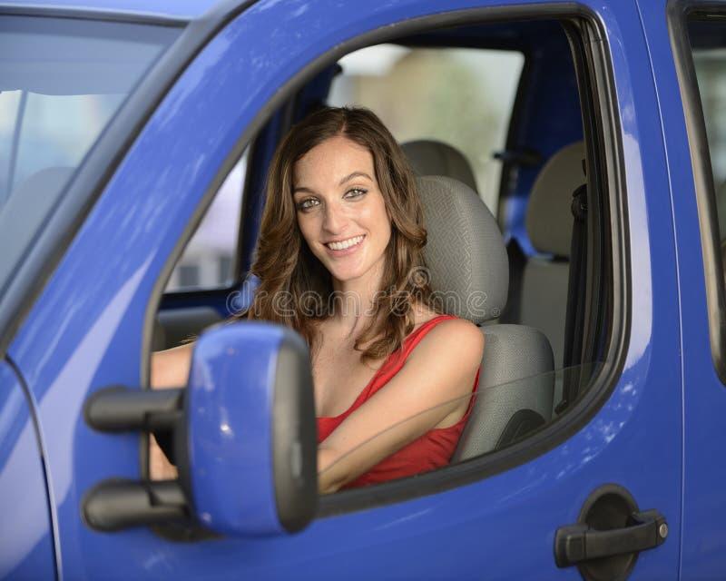 Γυναίκα που οδηγεί το νέο αυτοκίνητό της στοκ εικόνα