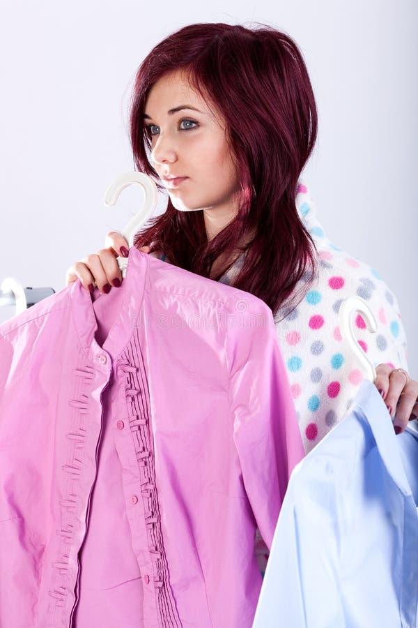 Γυναίκα που δοκιμάζει τα πουκάμισα επάνω στοκ εικόνα με δικαίωμα ελεύθερης χρήσης