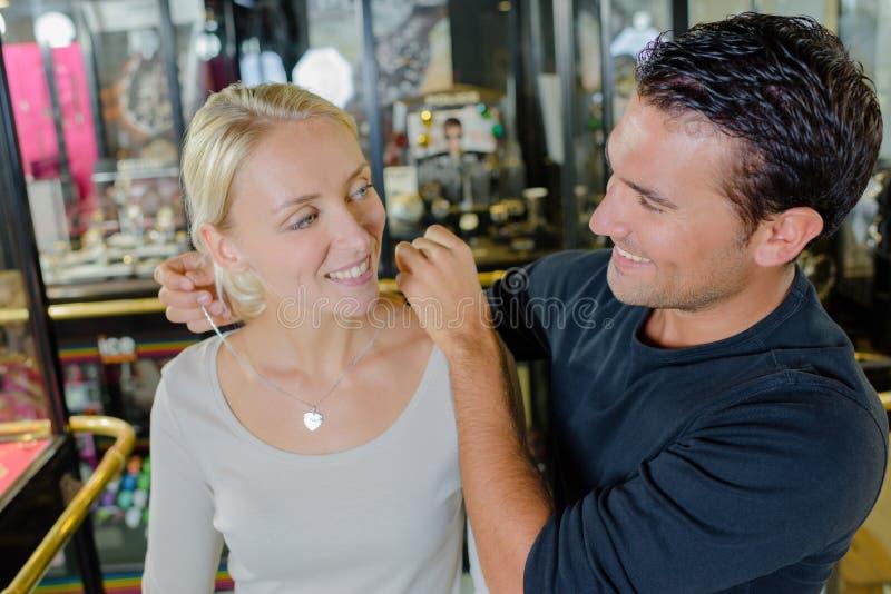 Γυναίκα που δοκιμάζει το περιδέραιο με το σύζυγο στο κατάστημα κοσμημάτων στοκ φωτογραφίες