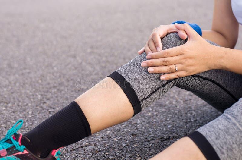 Γυναίκα που πάσχει από τον πόνο στα χέρια τραυματισμών ποδιών σχετικά με το γόνατό της μετά από τρέχοντας αθλητικής άσκησης και w στοκ φωτογραφία