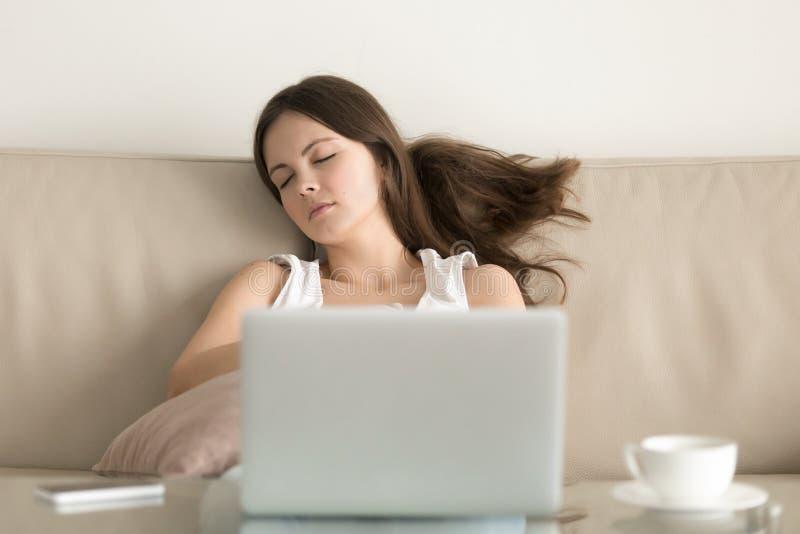 Γυναίκα που πέφτει κοιμισμένη στον καναπέ μπροστά από το lap-top στοκ εικόνες