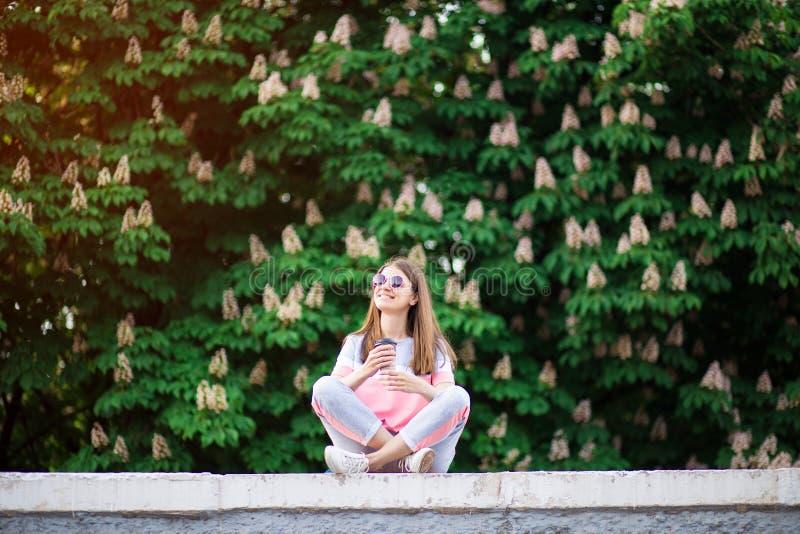 Γυναίκα που πίνει την καυτή φύση απόλαυσης καφέ υπαίθρια κατά τη διάρκεια των διακοπών στη θερινή ημέρα με το κάστανο στο υπόβαθρ στοκ φωτογραφία με δικαίωμα ελεύθερης χρήσης