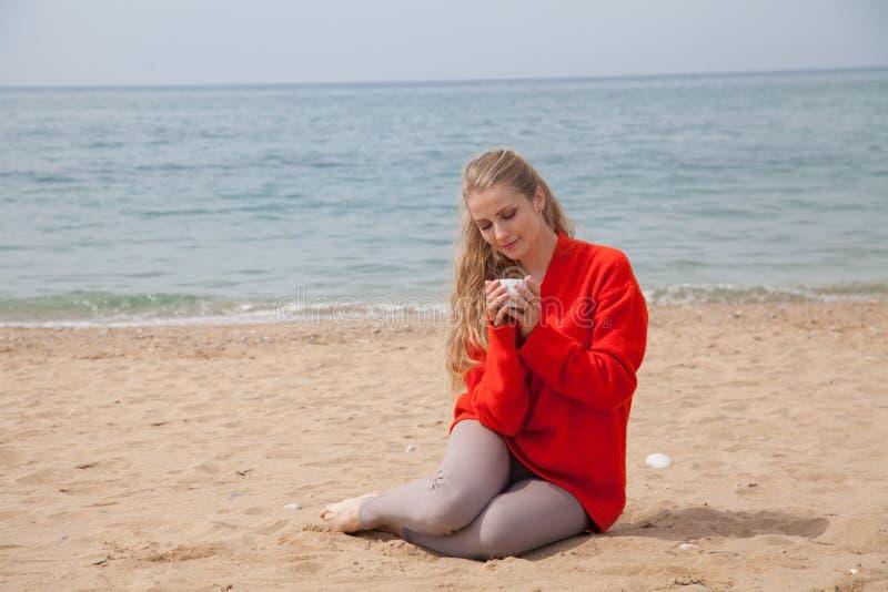 Γυναίκα που πίνει τον καυτό καφέ ή το τσάι στην αμμώδη παραλία στοκ φωτογραφία με δικαίωμα ελεύθερης χρήσης