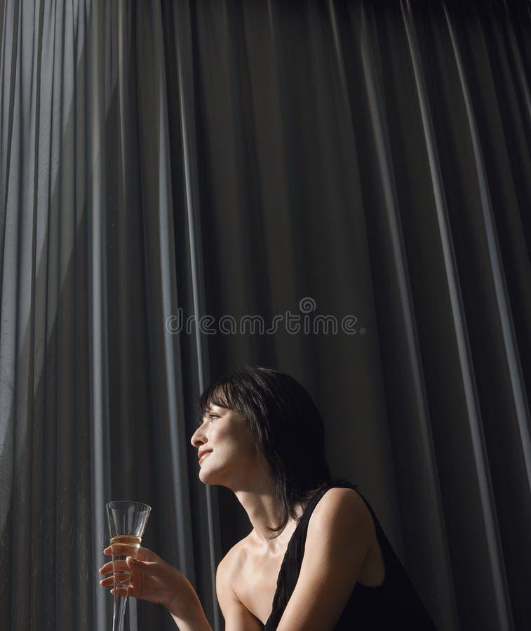 Γυναίκα που πίνει CHAMPAGNE μπροστά από τις κουρτίνες στοκ εικόνες