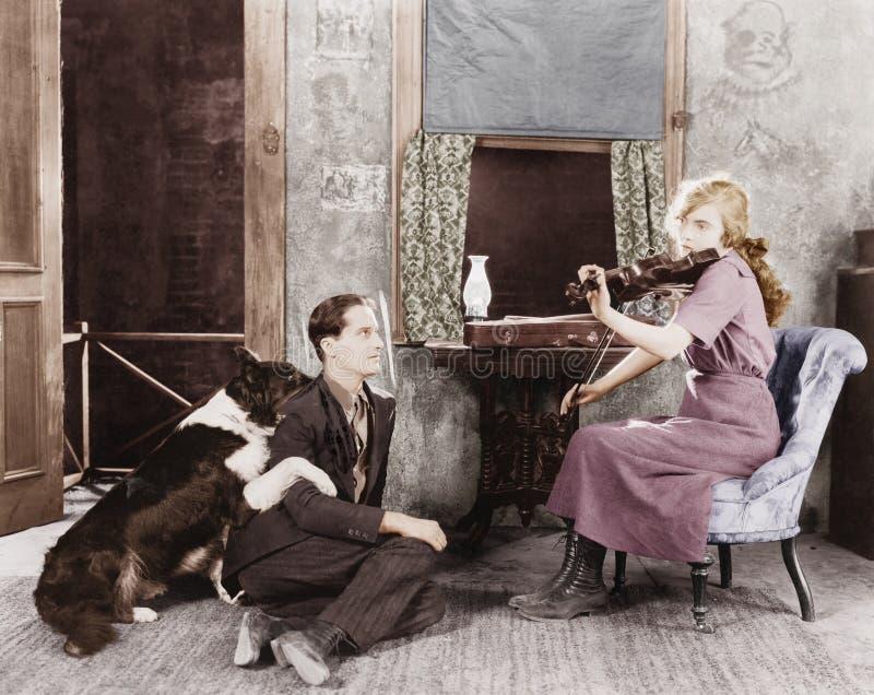 Γυναίκα που παίζει το βιολί για το φίλο και το σκυλί της (όλα τα πρόσωπα που απεικονίζονται δεν ζουν περισσότερο και κανένα κτήμα στοκ εικόνα με δικαίωμα ελεύθερης χρήσης