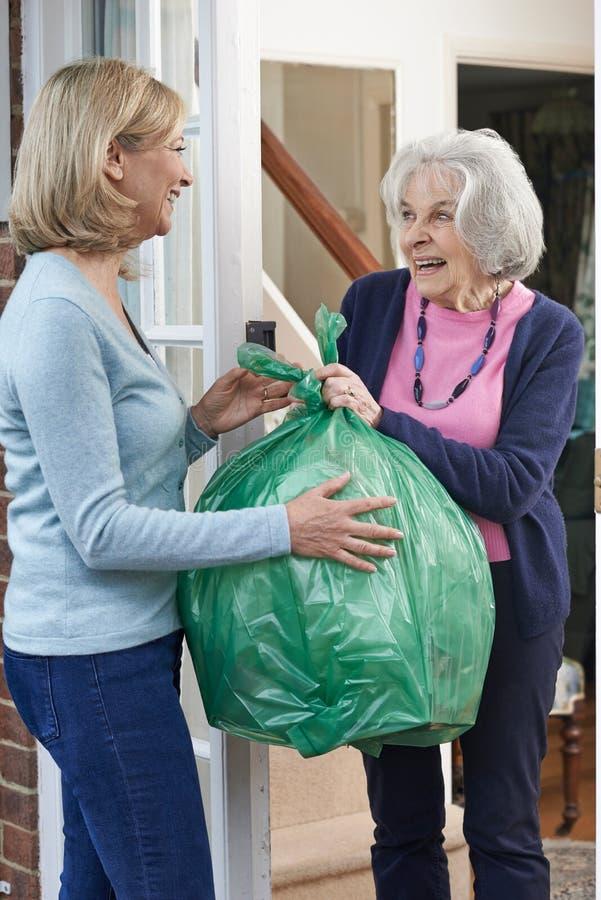 Γυναίκα που παίρνει έξω τα απορρίμματα για τον ηλικιωμένο γείτονα στοκ εικόνα