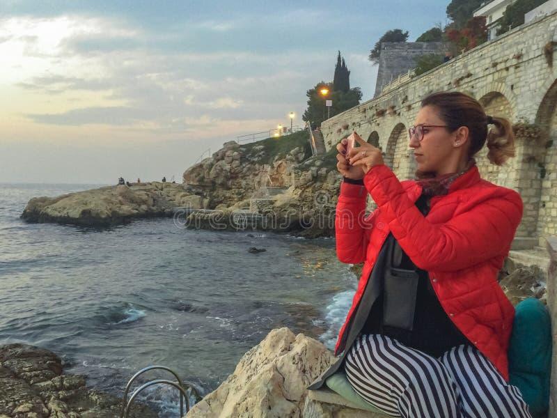 Γυναίκα που παίρνει μια εικόνα σε μια παραλία στο κέντρο πόλεων Rovinj στοκ εικόνες με δικαίωμα ελεύθερης χρήσης