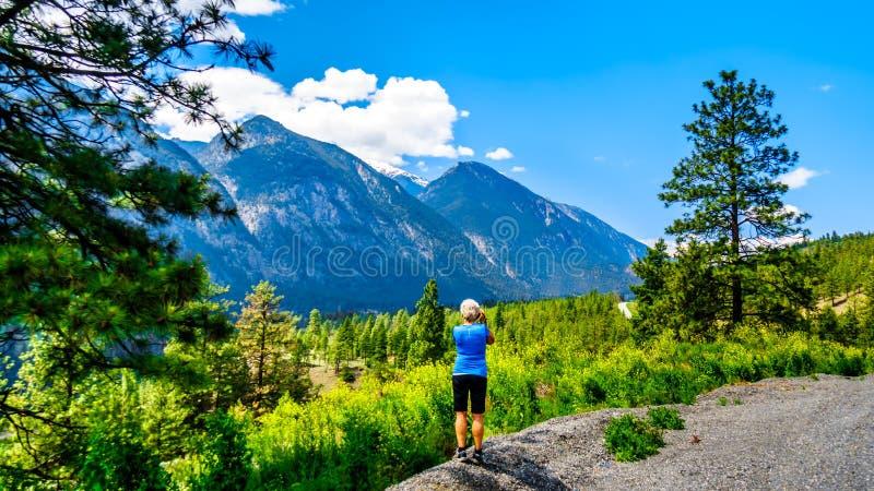 Γυναίκα που παίρνει μια φωτογραφία των τραχιών βουνών κατά μήκος του ποταμού Fraser και της εθνικής οδού lytton-Lillooet στοκ εικόνα