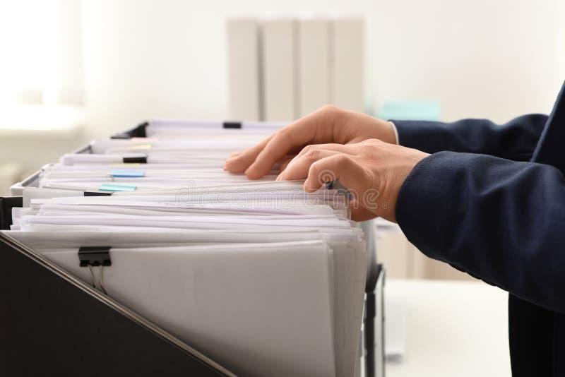 Γυναίκα που παίρνει τα έγγραφα από το φάκελλο στο αρχείο στοκ εικόνα