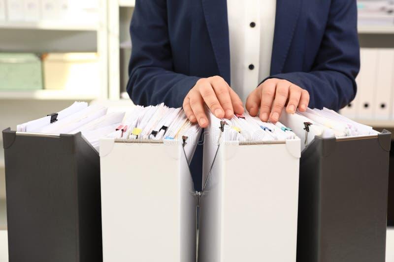 Γυναίκα που παίρνει τα έγγραφα από το φάκελλο στο αρχείο στοκ εικόνες