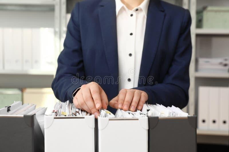 Γυναίκα που παίρνει τα έγγραφα από το φάκελλο στο αρχείο στοκ εικόνες με δικαίωμα ελεύθερης χρήσης