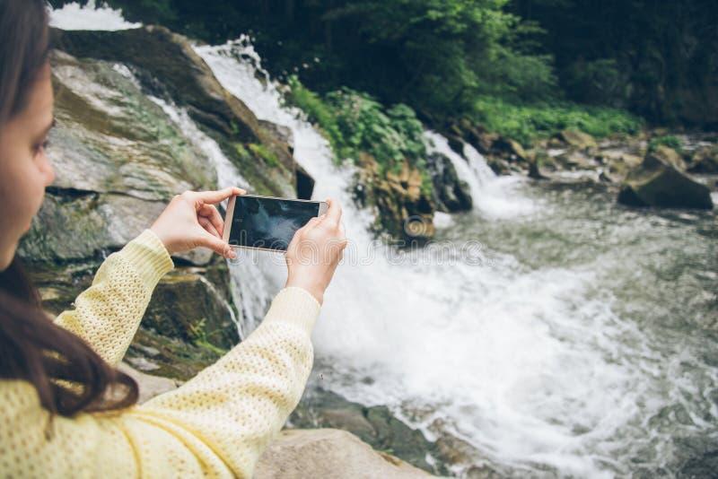 Γυναίκα που παίρνει την εικόνα στο τηλέφωνο του καταρράκτη στο υπόβαθρο στοκ φωτογραφίες με δικαίωμα ελεύθερης χρήσης