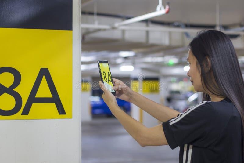 Γυναίκα που παίρνει την εικόνα στο υπαίθριο σταθμό αυτοκινήτων για να επισημάνει κάτω από το χώρο στάθμευσης της στοκ εικόνες