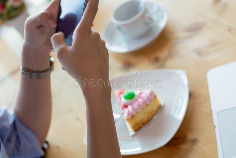 Γυναίκα που παίρνει την εικόνα του κέικ φραουλών με το smartphone στοκ εικόνες