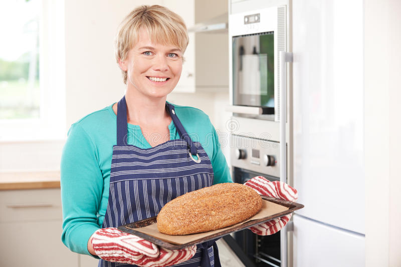 Γυναίκα που παίρνει την κατ' οίκον ψημένη φραντζόλα από το φούρνο στοκ εικόνες
