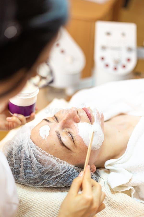 Γυναίκα που παίρνει την του προσώπου προσοχή από το beautician στο σαλόνι SPA στοκ φωτογραφία με δικαίωμα ελεύθερης χρήσης