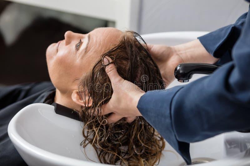 Γυναίκα που παίρνει την τρίχα πλυμένη στο σαλόνι στοκ εικόνες