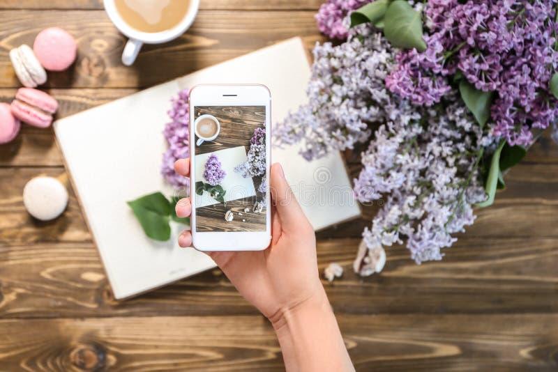 Γυναίκα που παίρνει τη φωτογραφία της ανθίζοντας πασχαλιάς και του φλυτζανιού με τον καφέ στοκ εικόνες με δικαίωμα ελεύθερης χρήσης