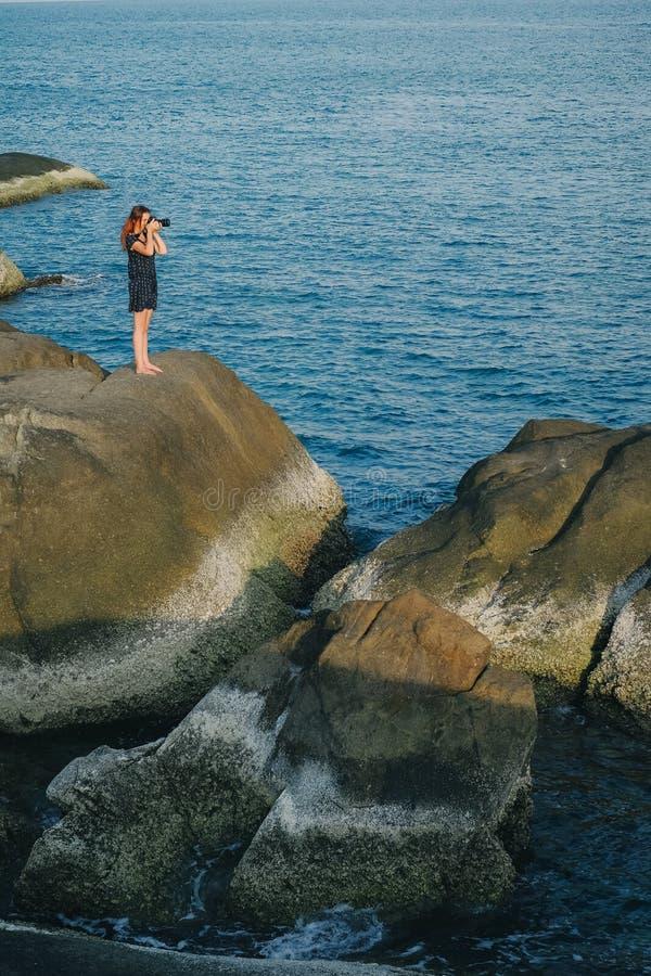 Γυναίκα που παίρνει τη φωτογραφία της όμορφης μπλε θάλασσας από τον απότομο βράχο στοκ εικόνα