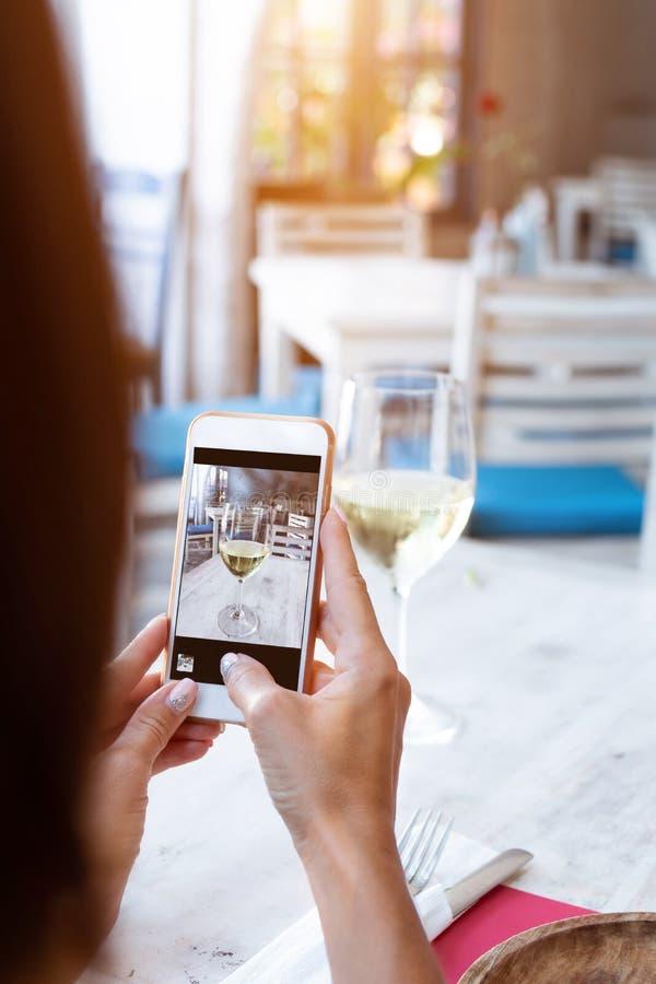 Γυναίκα που παίρνει τη φωτογραφία του άσπρου κρασιού στο smartphone της στο εστιατόριο στοκ φωτογραφίες