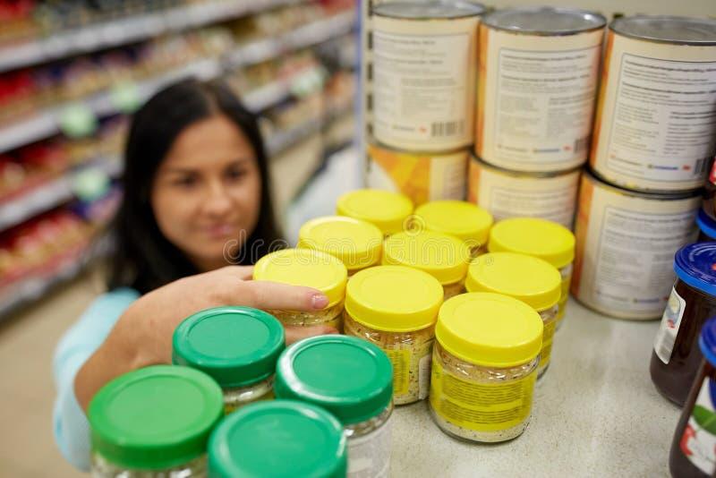 Γυναίκα που παίρνει το βάζο με τα τρόφιμα από το ράφι στο παντοπωλείο στοκ φωτογραφία